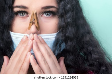 girl with a clothespins on the nose in a protective medical mask, the concept of cold and runny nose