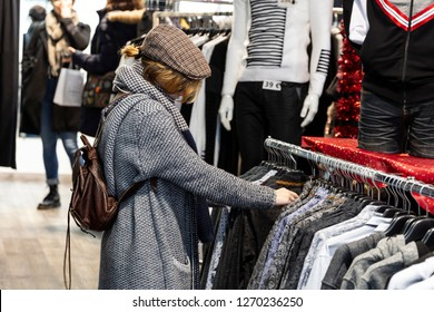A girl in a clothing shop doing shopping and looking for a man's shirt