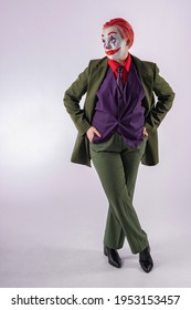 A girl in clown makeup (white face, red smile to the ears and blue diamonds on the eyes), with red hair, in a green jacket, red shirt, green trousers, purple vest and tie. Сlown animator for children.