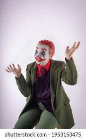A girl in clown makeup (white face, red smile to the ears and blue diamonds on the eyes), with red hair, in a green jacket, red shirt, green trousers, purple vest and tie. Happy clown animator