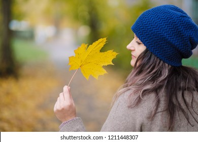 The girl in a coat and blue hat on a background of autumn trees and maple leaves. City street, September day. Yellow, red and green leaves.