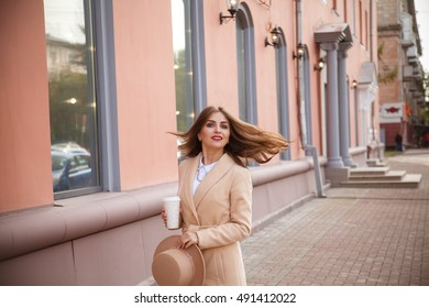 The girl in a coat, hat and coffee on a background of city streets