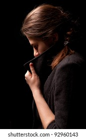 The girl in the coat on a black background
