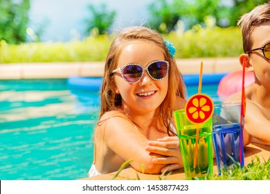 Girl with cocktail during pool party in summer