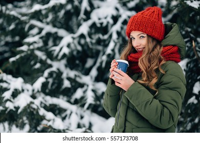 Girl with coffee. Happy young girl drinking coffee in winter cold day. Girl in red hat and scarf drinking coffee outdoors in winter weather.