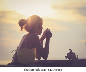 Girl and coffee in the morning at the beach / soft focus picture / Vintage concept