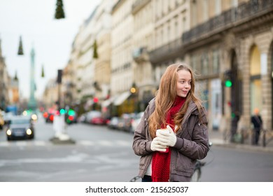 Girl with coffee on a Parisian street decorated for Christmas