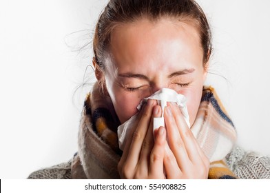 Girl with cold sneezing in handkerchief wearing scarf and sweater