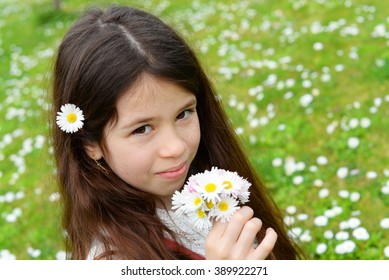 Girl collecting flowers on a lawn