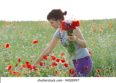 girl collecting poppies and cornflower from a summer field.