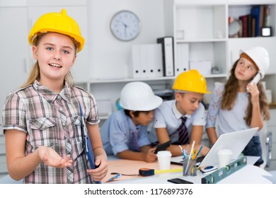 Girl in color helmet builder with collective architects near notebook