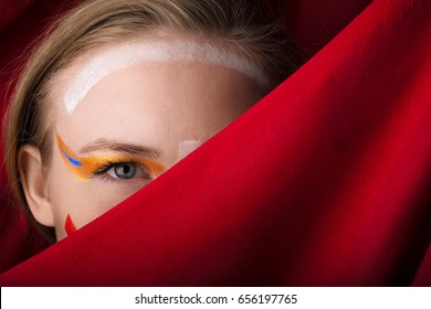 Girl with color make-up on a red background. A blonde with colored make-up peeks out because of the red cloth.