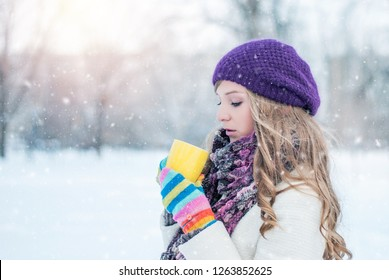 Girl with colored gloves in the snow drinking tea