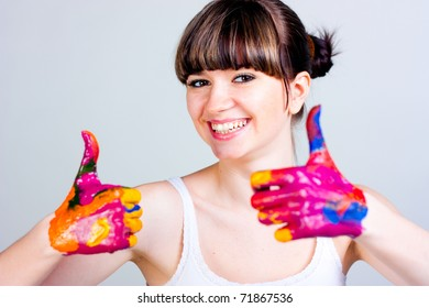 A girl with colored hands on a gray background