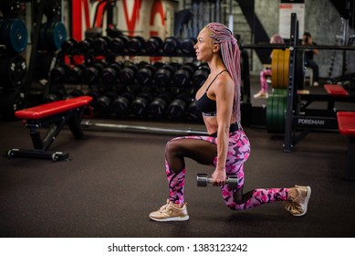 Girl in colored sportswear does exercises with dumbbells in the gym. Young beautiful woman with African braids doing lunges with dumbbells