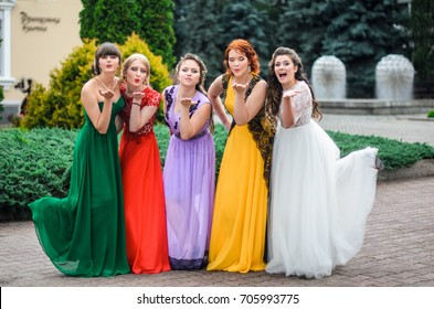 girl in colorful ball gowns dancing in the city. Hair and makeup for prom