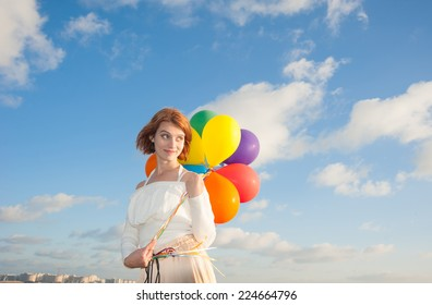 girl with colorful balloons on the beach