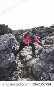 Girl in colorful down jacket climbing rocks at sunrise in Grampians National Park, Victoria, Australia.