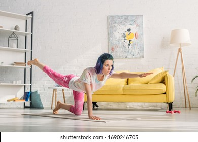 Girl with colorful hair doing asana with outstretched hand and raised leg on yoga mat in living room