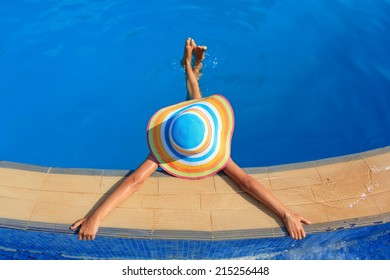 Girl with colorful hat in the pool