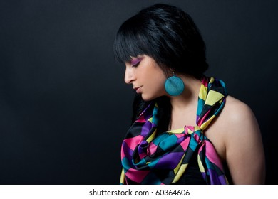 Girl with colorful scarf smiling and posing in front of black background