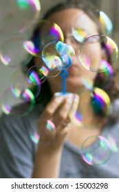 Girl with lot of colorful soap bubbles