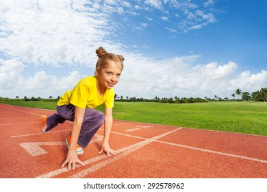 Girl in colorful uniform on start ready to run