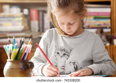 Girl coloring on paper having creative time at home