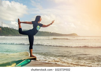 A girl in the colourful dress on the beach is doing yoga, Galle, Sri Lanka
