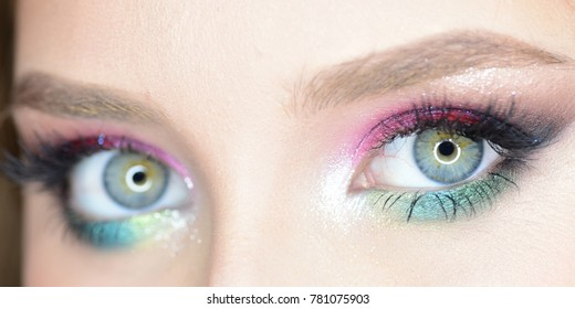 Girl with colourful makeup and beautiful eyebrows, close up. Eyes of lady with seductive look. Model wearing pink and green shades. Cosmetics and fashion concept.
