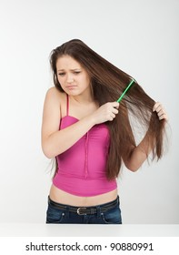 girl combs her hair hard and winces in pain