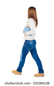 Girl comes with  stack of books.back view. Rear view people collection.  backside view of person.  Isolated over white background. Girl in a white jacket carries the book goes to the right.