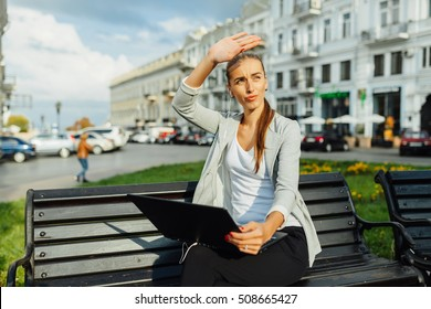 the girl communicates with the interlocutor. on the street fine weather. The girl covers a face from the sun which very pleasantly warms her, but prevents to communicate.