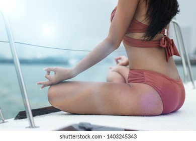 Girl with confidence exercises with yoga poses in swimwear on board a private yacht vacation.