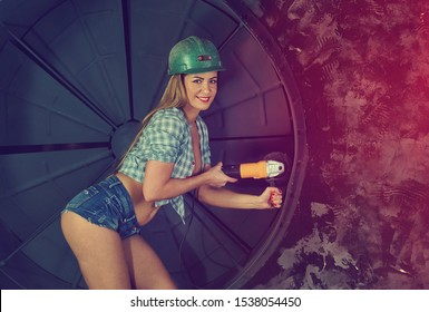 girl in construction clothes and protective equipment posing  on grunge background