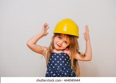 girl with construction tools. Little girl in polka-dot dress. little girl in a helmet. Child protection and safety. girl with construction tools. baby building. little girl making repairs.