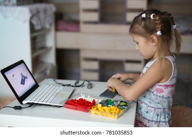 The girl constructs a robot from the designer and using a laptop, home furnishings, light tone