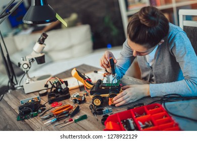Girl constructs technical toy. Technical toy on table full of details