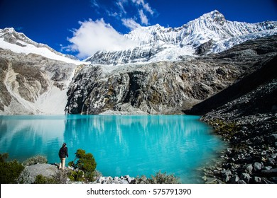A Girl contemplating the color of Laguna 69, with the great Nevado Chacraraju mountain in the background. Huascaran National Park - Huaraz - Peru