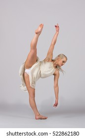 Girl contemporary dancer in studio against a white background in a creme colored dress
