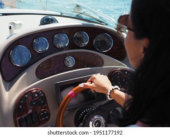 The girl controls a cruise yacht holding her hand on the steering wheel on a summer sunny day. Close-up photo