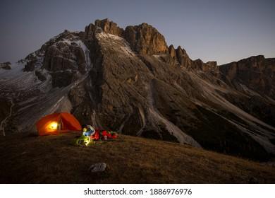 Mädchen kocht das Abendessen vor dem Zelt