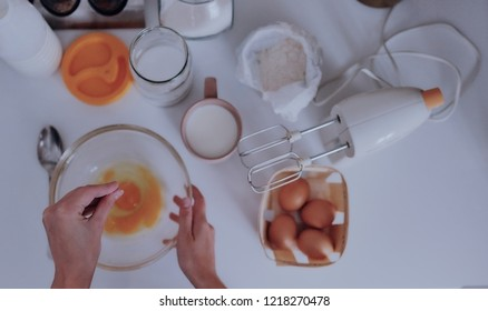 The girl cooks pancakes in the kitchen. Pour salt in a bowl with eggs. Nearby there is a mixer, flour, sugar, salt.