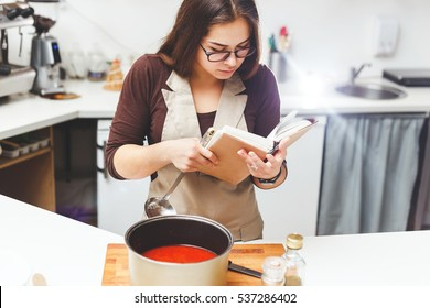 Girl cooks tomato soup recipes according to the book