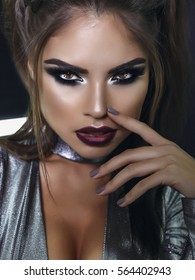 girl with cool fashionable make-up posing in studio,matte lips and nails,cate eyes,smokey eyes, beautiful make up and curly hair style over holiday dark background with magic glow. Holiday celebration