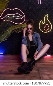 Girl with a cornrows hairstyle, wearing denim jacket and sunglasses, sits on the floor in a club at the wall made of rabitz net, covered with neon lamps. Commercial, fashionable, conceptual design