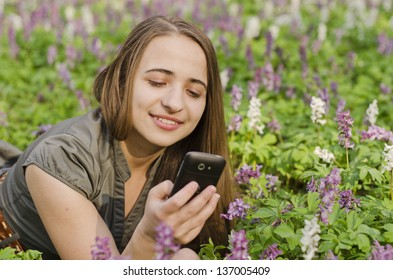 Girl in corydalis is looking at mobile