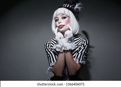 Girl in costume for Halloween holding.Sexy female in dress on gray background. Happy Halloween on the World. Holiday clown. - Shutterstock ID 1366406075