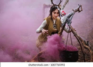 Girl in costume with horns doing some stuff near the steaming boiler with colorful smoke. Halloween, samhain