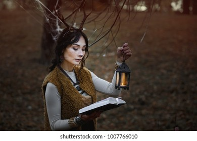 Girl in costume with horns faun  with a flashlight  in her hands posing in the autumn forest. Halloween, samhain